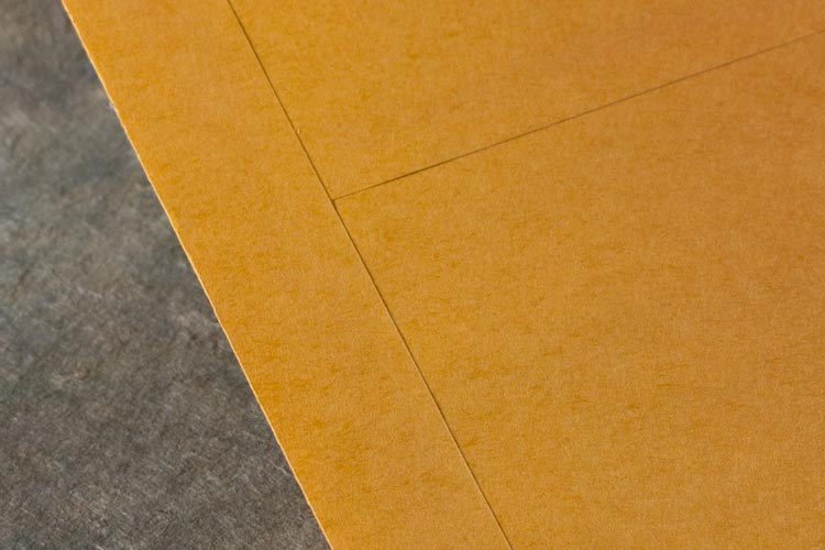 Kraft paper and center-seam construction provide protection during filing and mailing