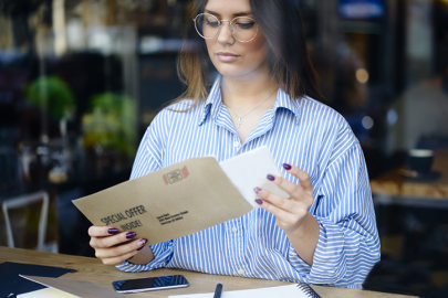 girl using mobile to view direct mail coupon
